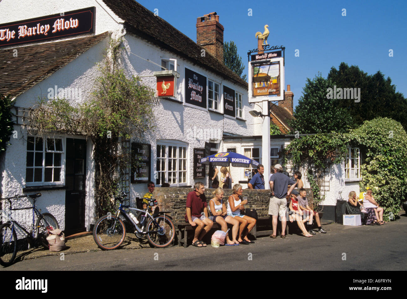 The Barley Mow country village pub with people sat outside on hot sunny summer's day enjoying sunshine. Tilford - Stock Image