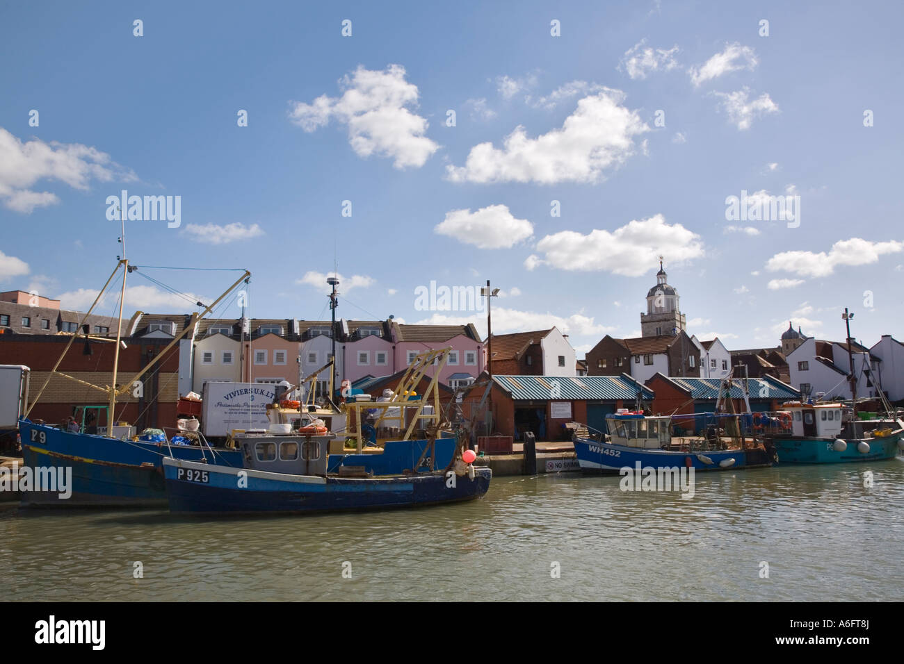 Town Camber fish docks with colourful fishing boats in water and modern housing development Old Portsmouth Hampshire Stock Photo