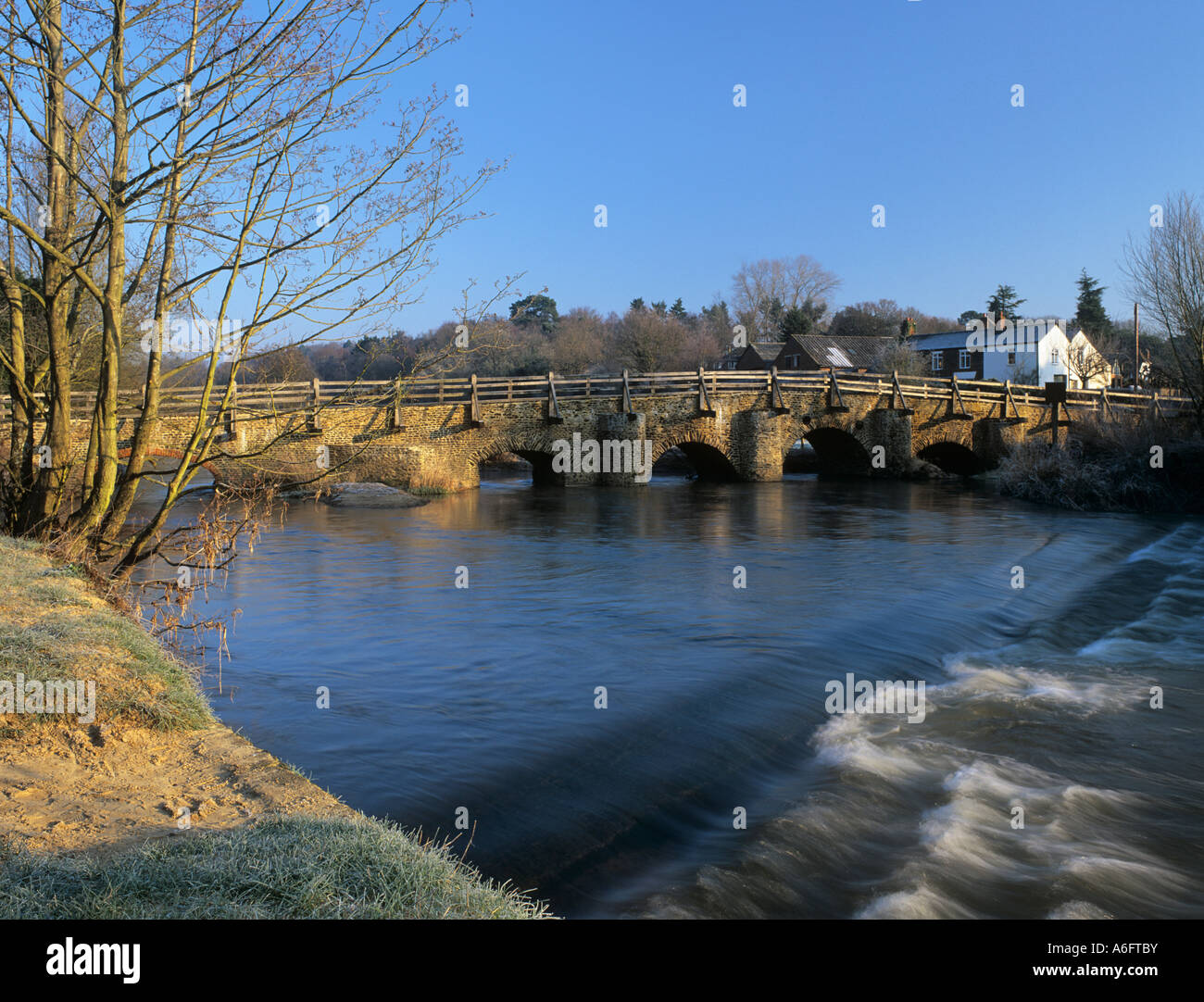 River Wey and old east bridge in historic country village of Tilford Surrey England UK britain - Stock Image