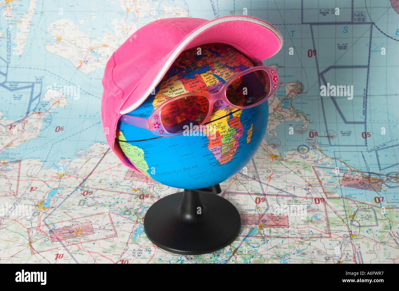 Globe with sunglasses and cap in front of a aeronautical chart, symbol for world-tour and travel - Stock Image