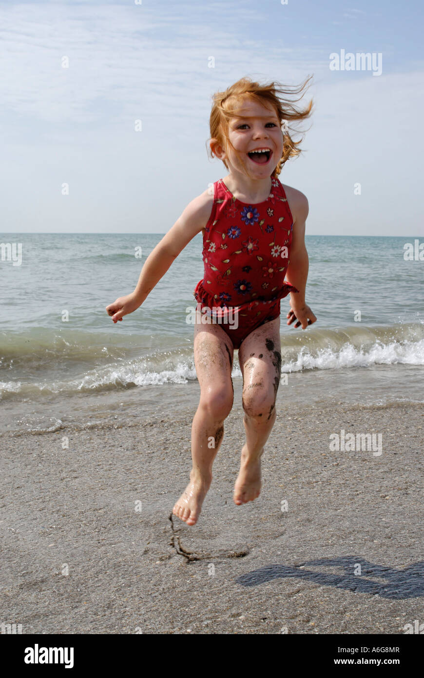 Child hops at the beach in the sea surf - Stock Image