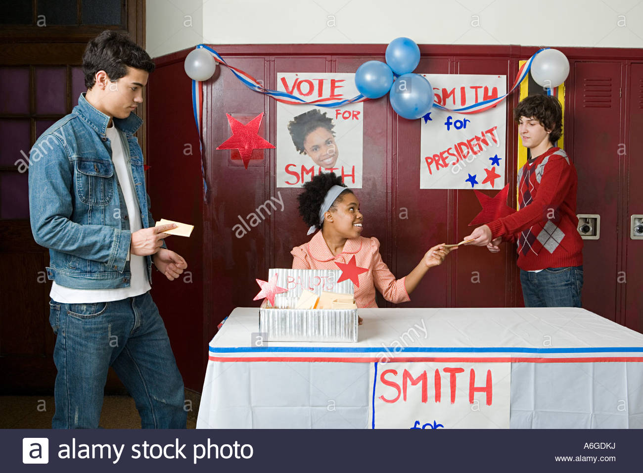 Boys giving votes to girl - Stock Image