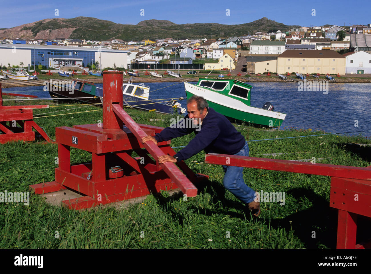 Man using cabestan, a  traditional boat winch, to haul his boat on shore. - Stock Image