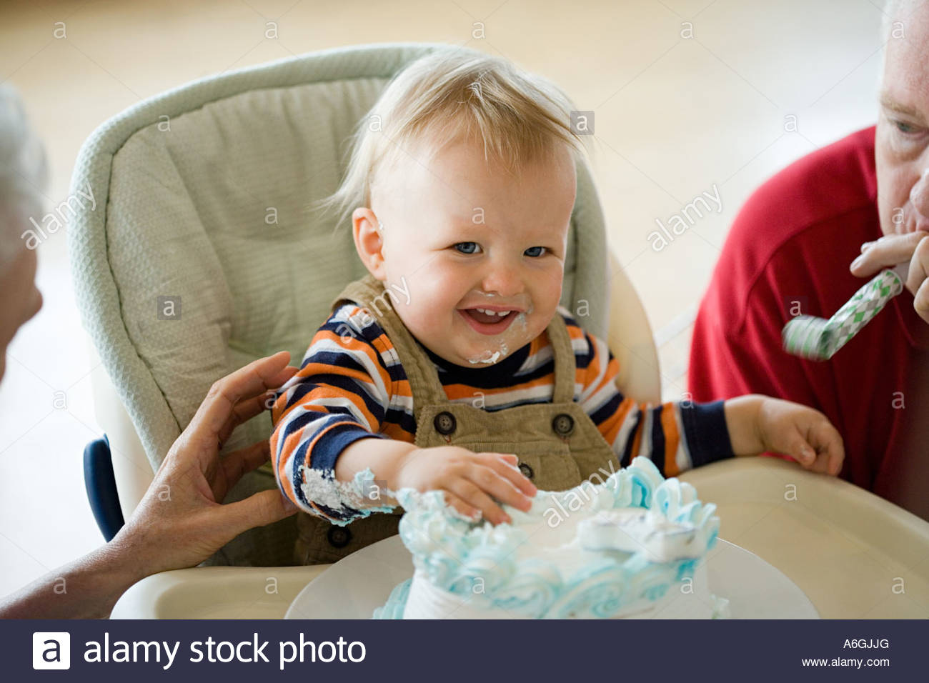 Messy one year old with birthday cake - Stock Image