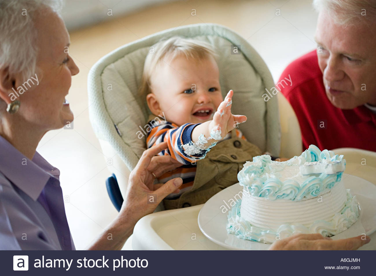 Grandparents and messy baby with cake - Stock Image