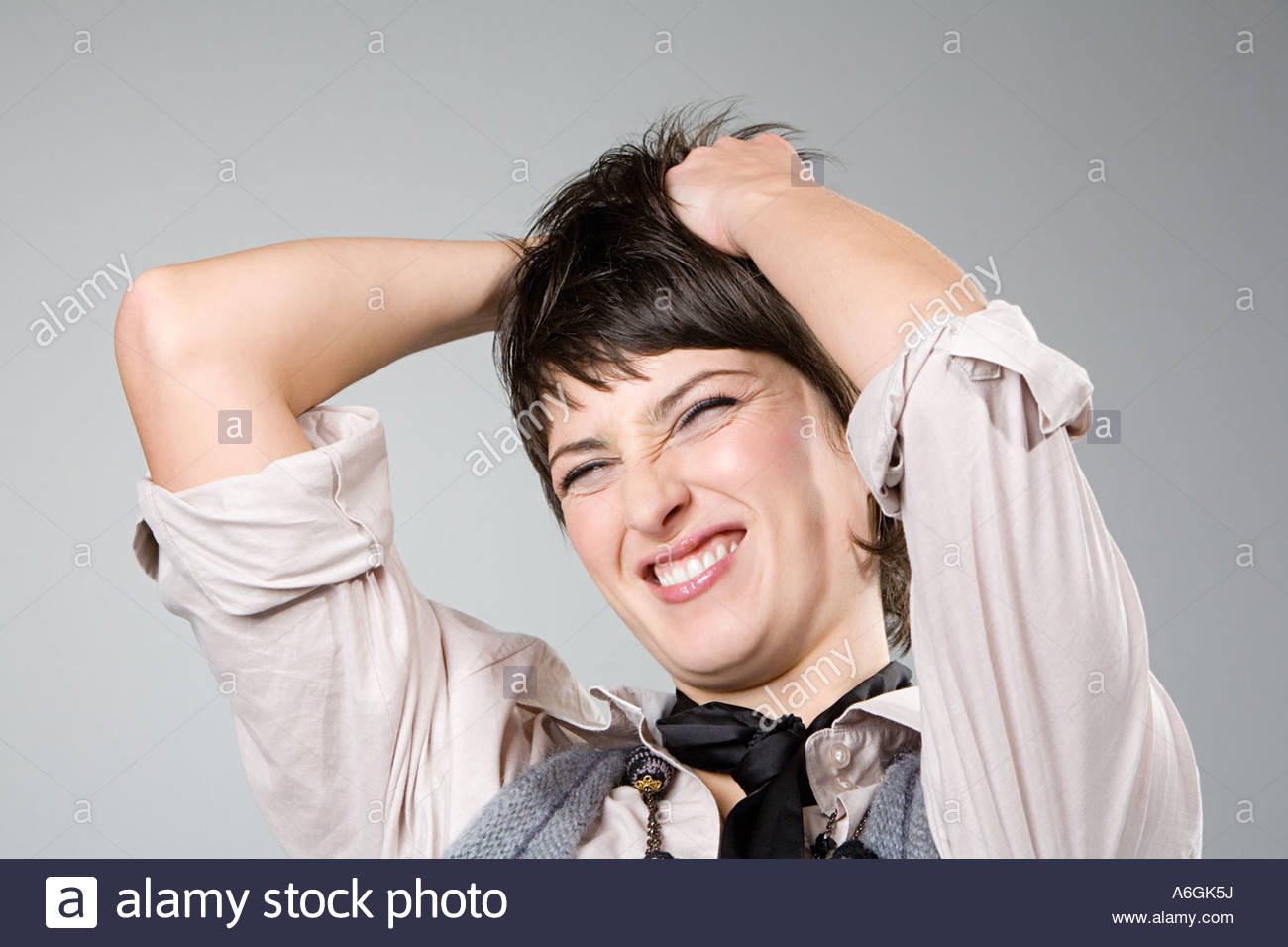 Woman messing with her hair - Stock Image