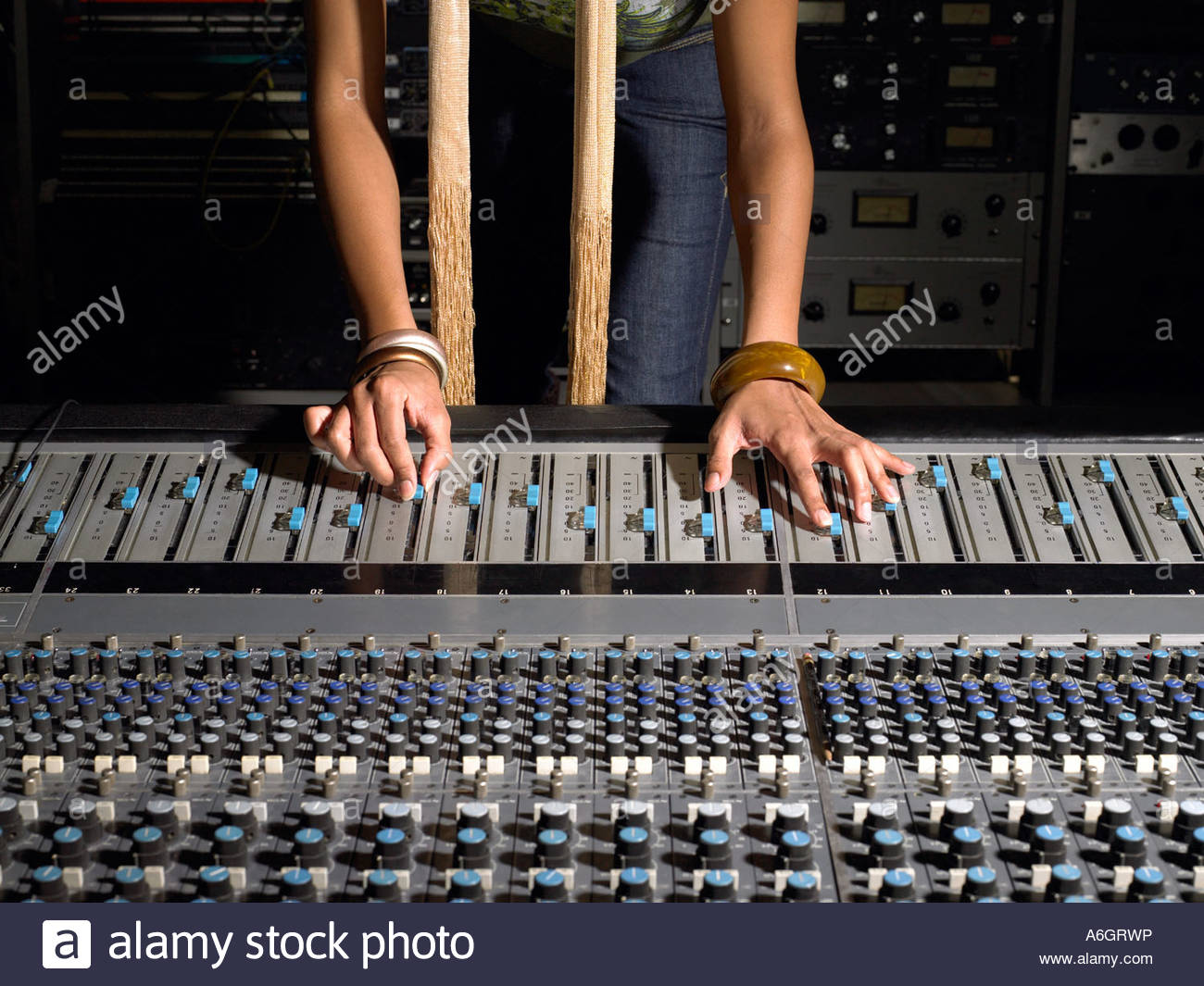 Woman using mixing desk Stock Photo