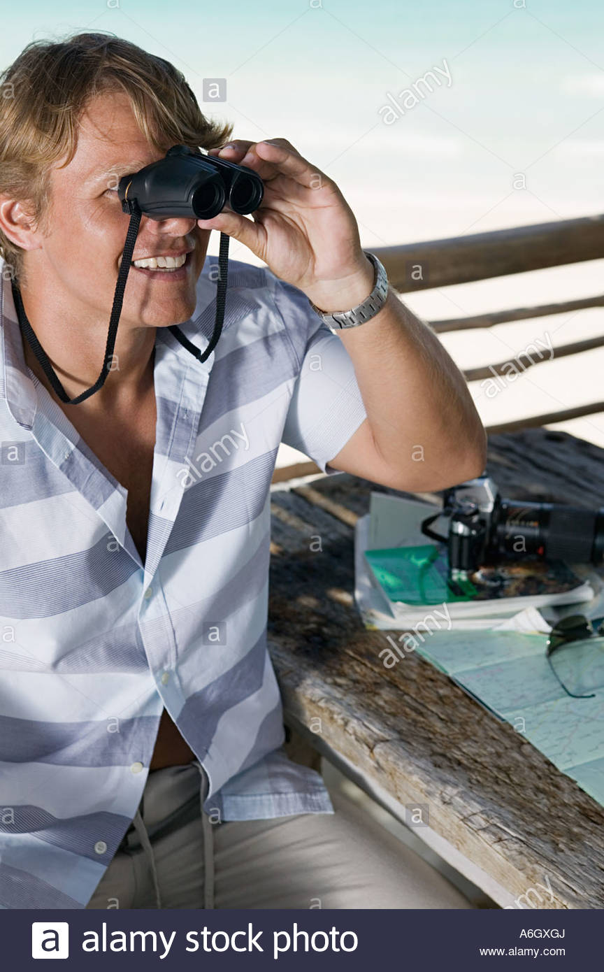 Man looking through binoculars - Stock Image