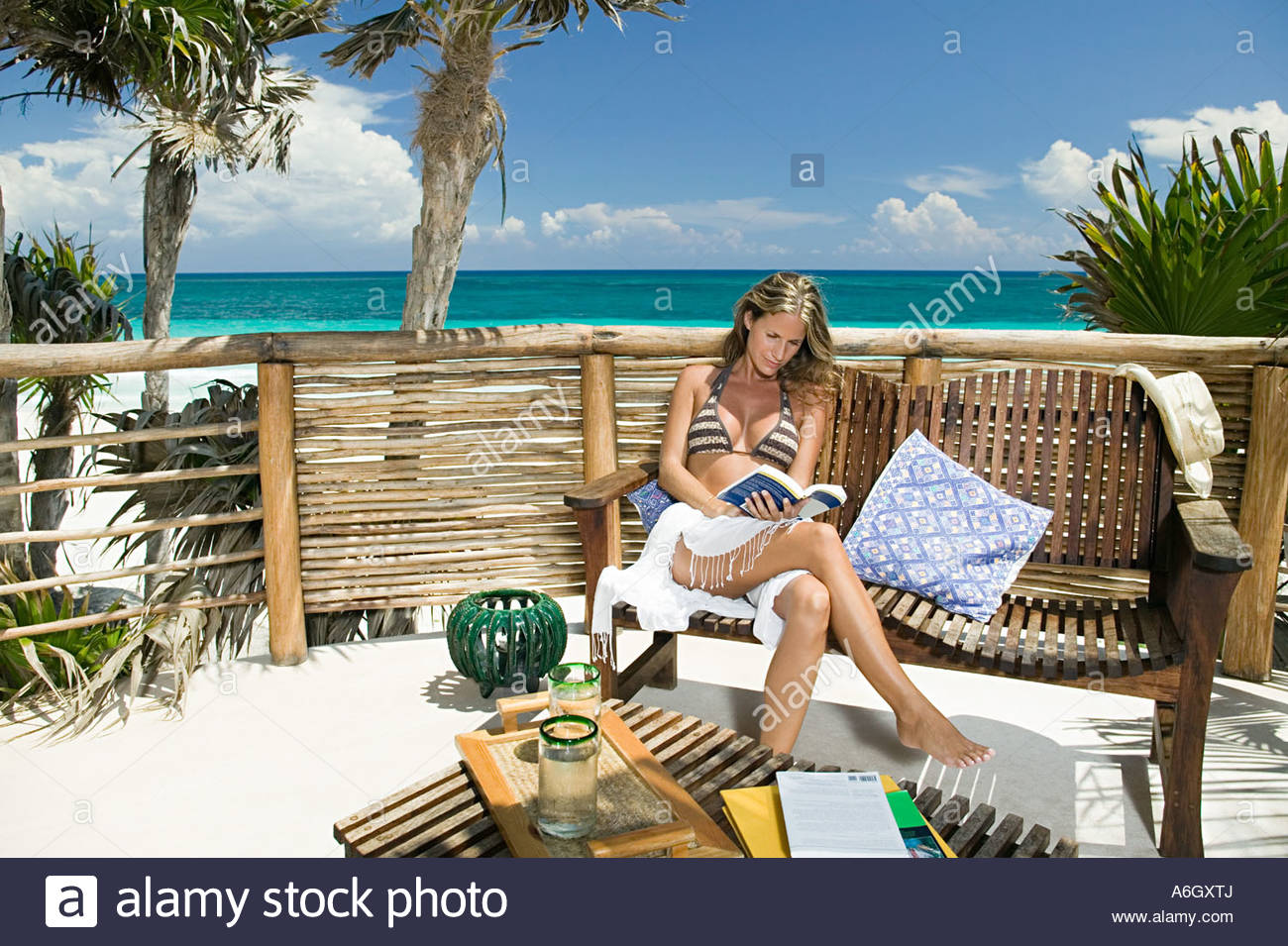 Woman reading a book by beach - Stock Image