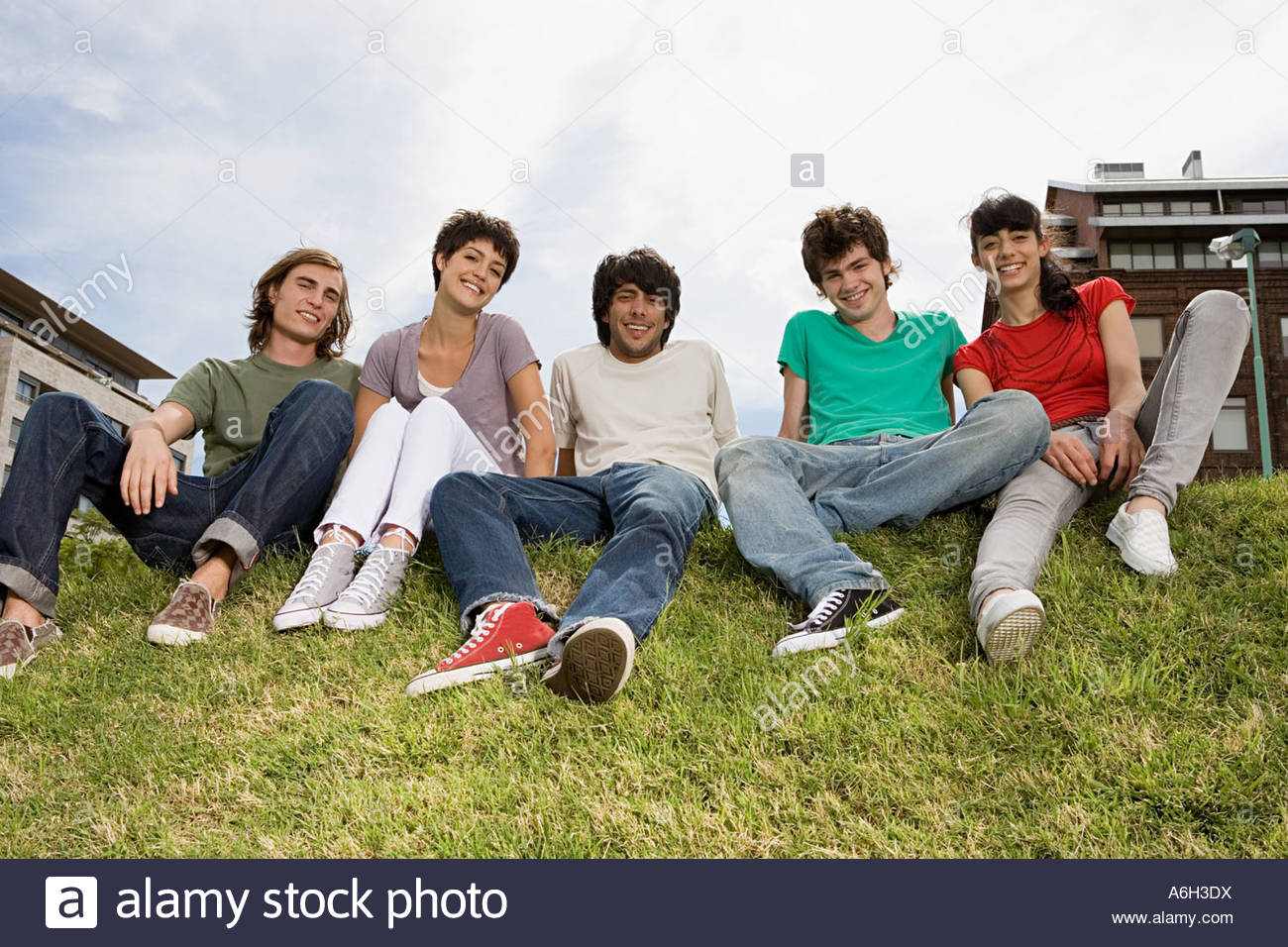 Friends sitting on grass verge - Stock Image