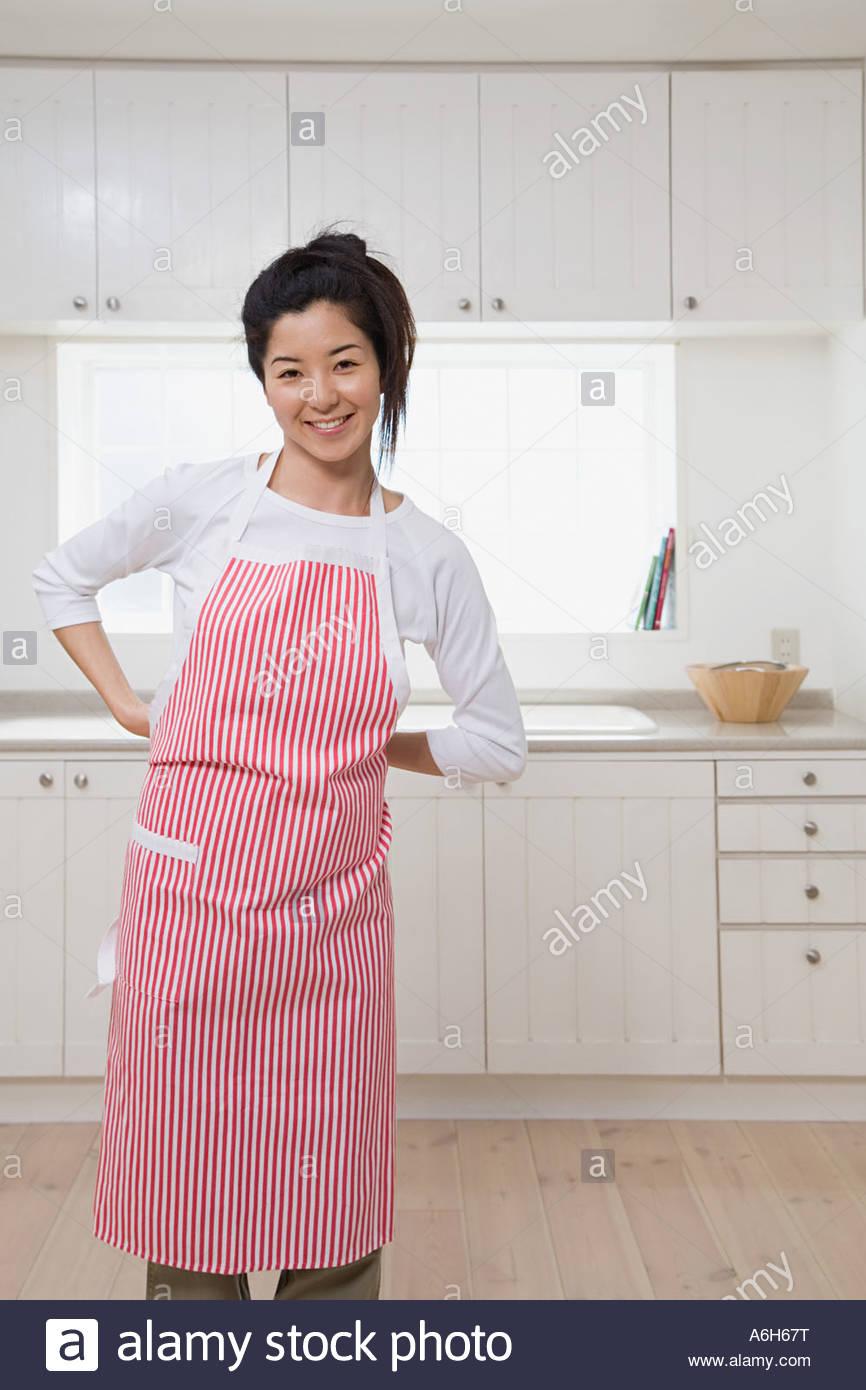 Woman putting apron on - Stock Image