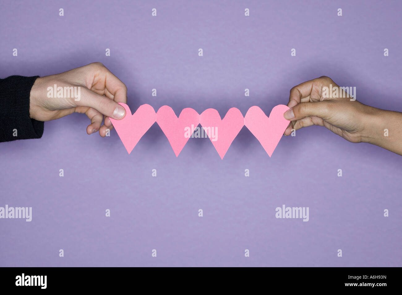 Close Up Of Two Mixed Race Hands Holding Pink Paper Cut Out Hearts In Between Them