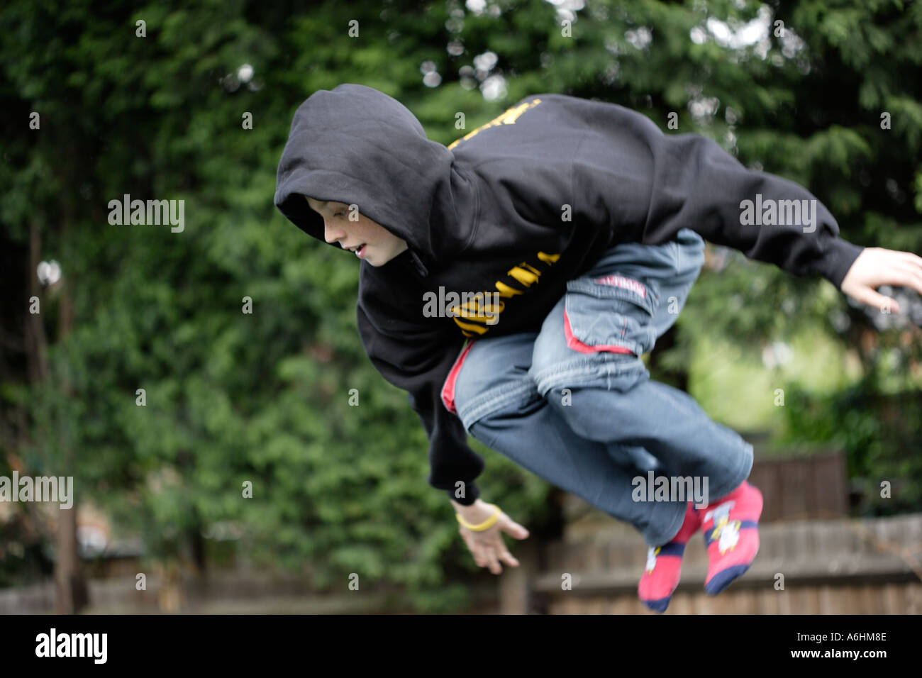 Teenager wearing hoody on trampoline, in suburban garden. - Stock Image