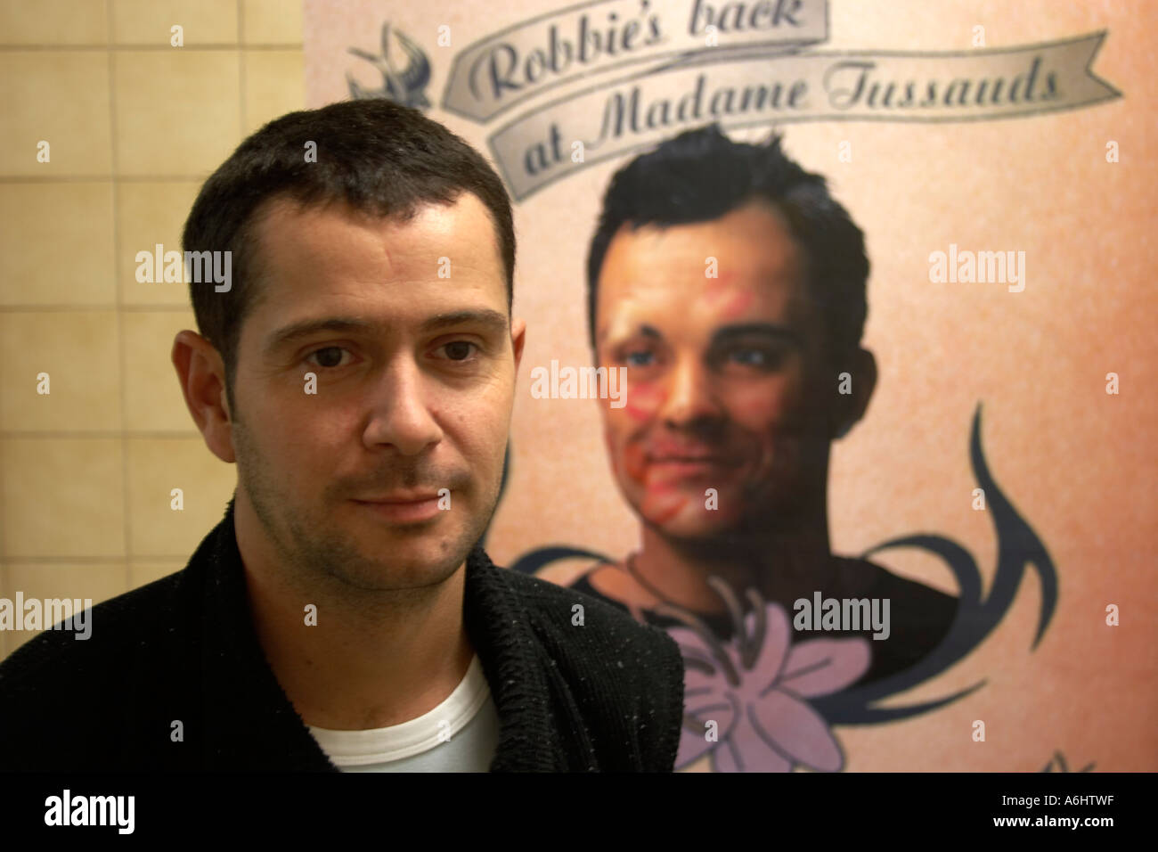 Rbbie Williams lookalike with a poster on the underground - Stock Image