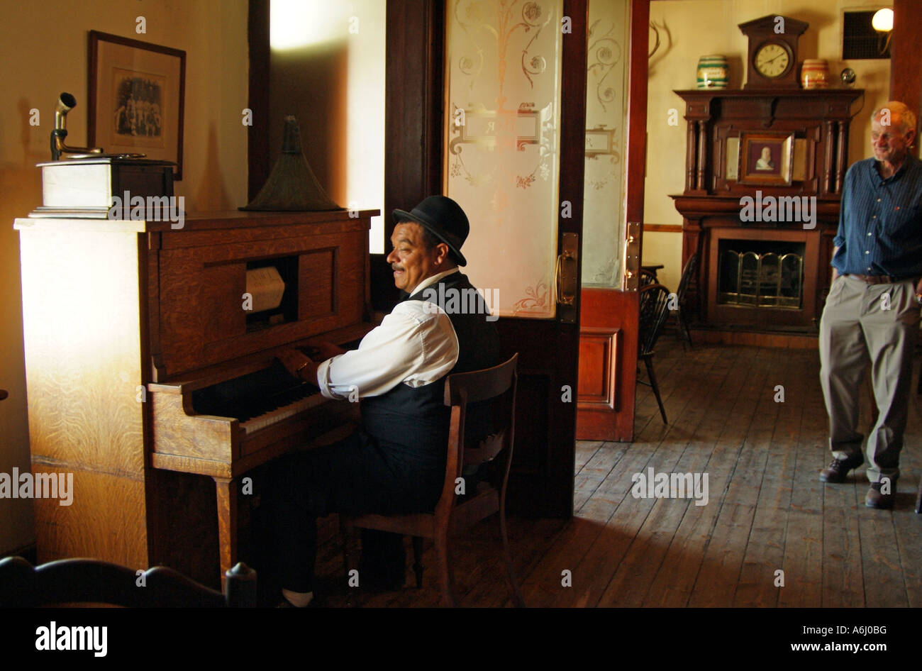 Pianist wearing a bowler hat playing in an old Edwardian pub bar South  Africa RSA 63222155660