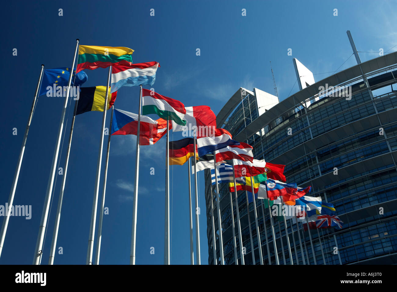Flag poles with flags of the European Union countries blow before the building of the European parliament in Strasbourg, France - Stock Image