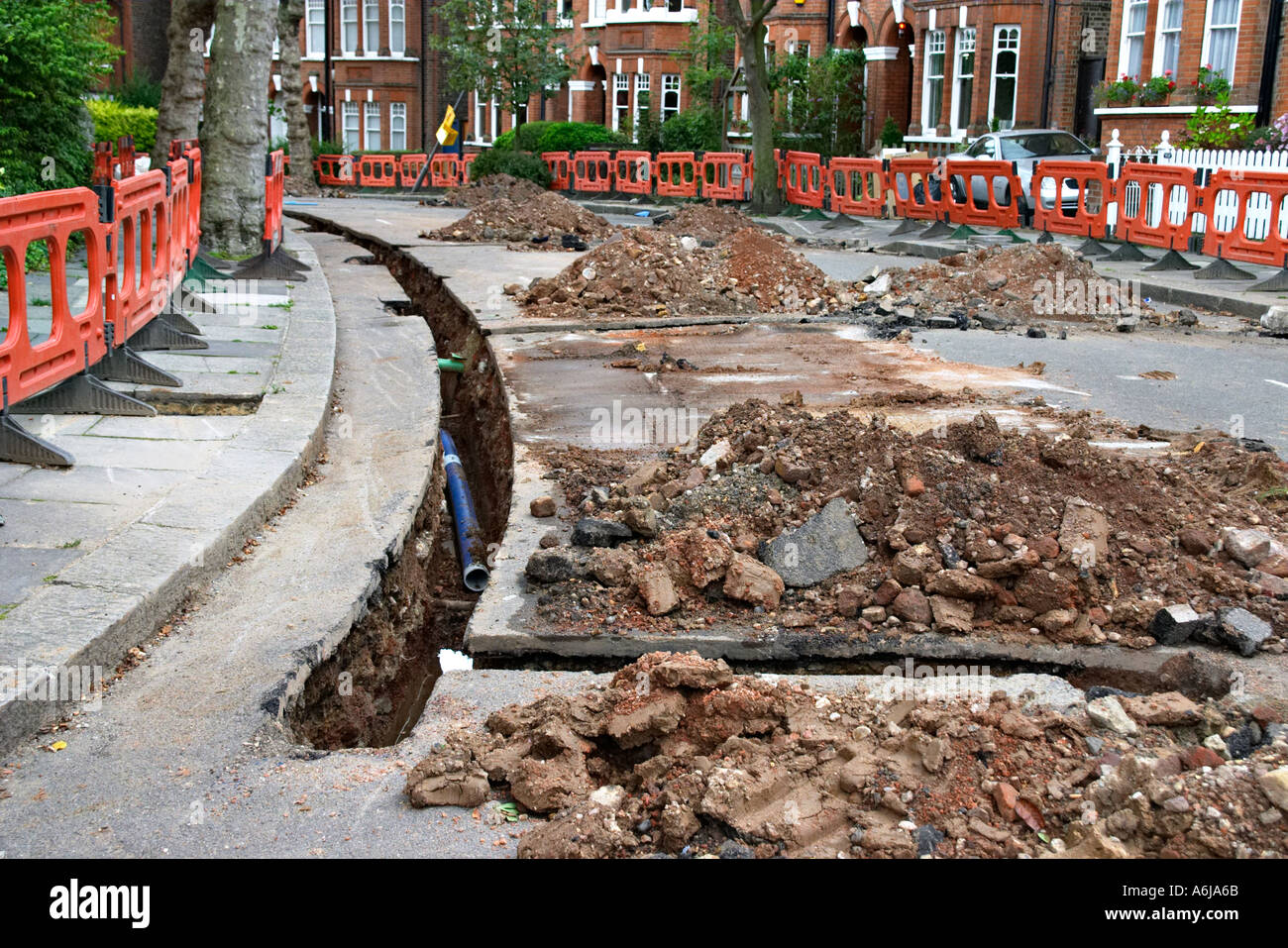sewer sewerage gas mains water supply road works repair street crater dig digging pipe pipework roadworks cable - Stock Image