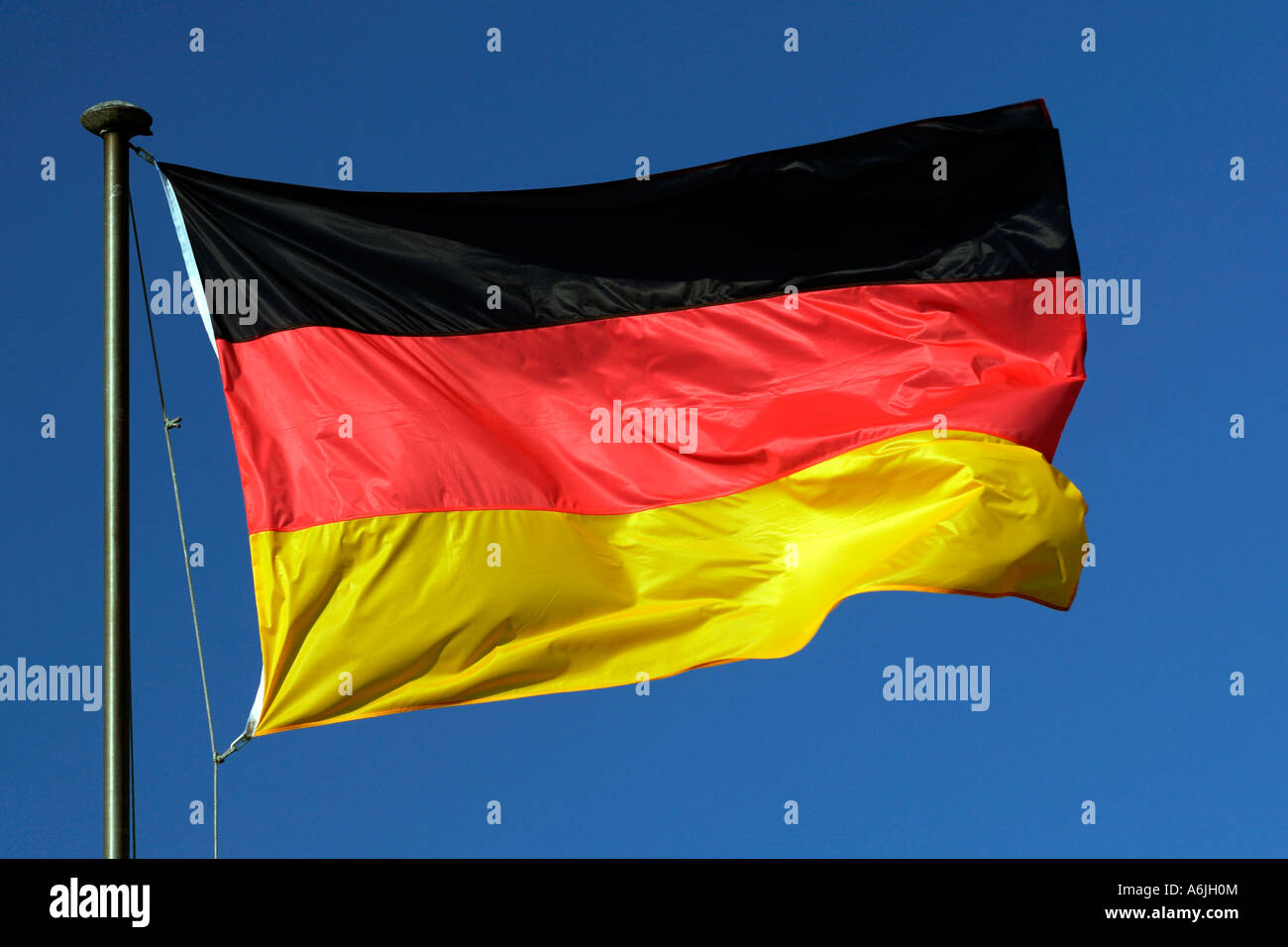 German national flag against blue sky - Stock Image