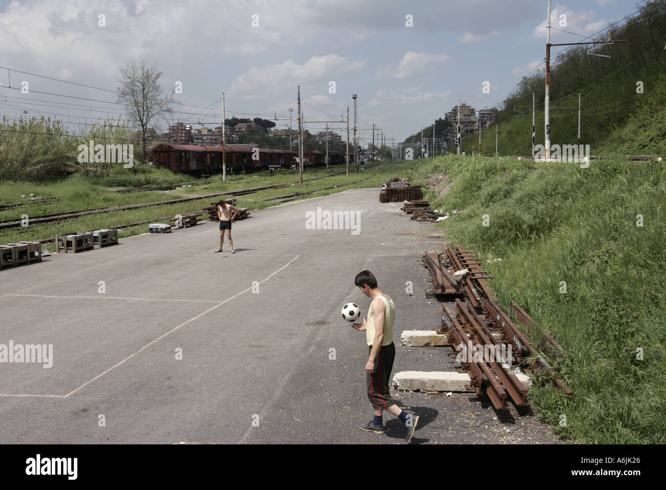 Two men playing football in a disused train station Rome italy - Stock Image