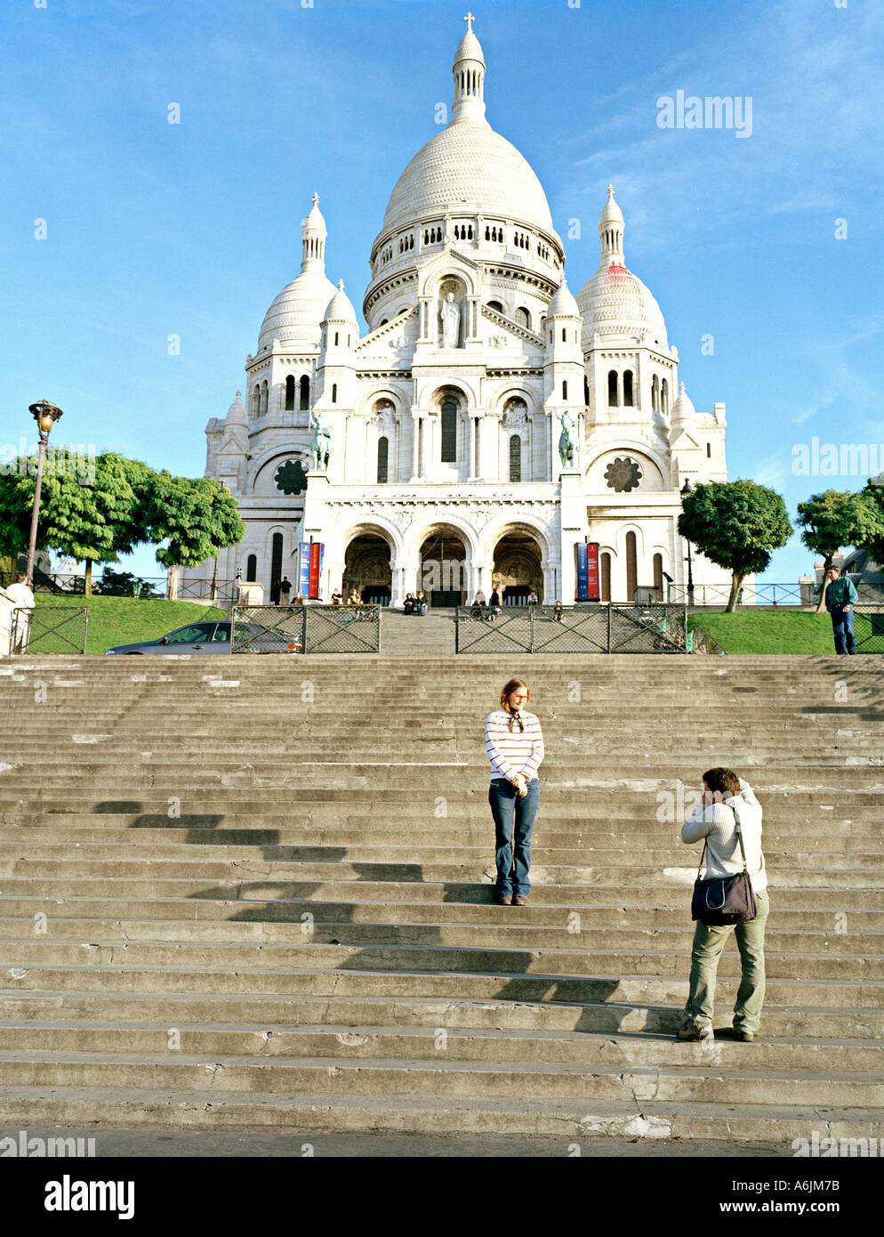 couple taking pictures in front of Sacre Coeur Basilica Paris - Stock Image