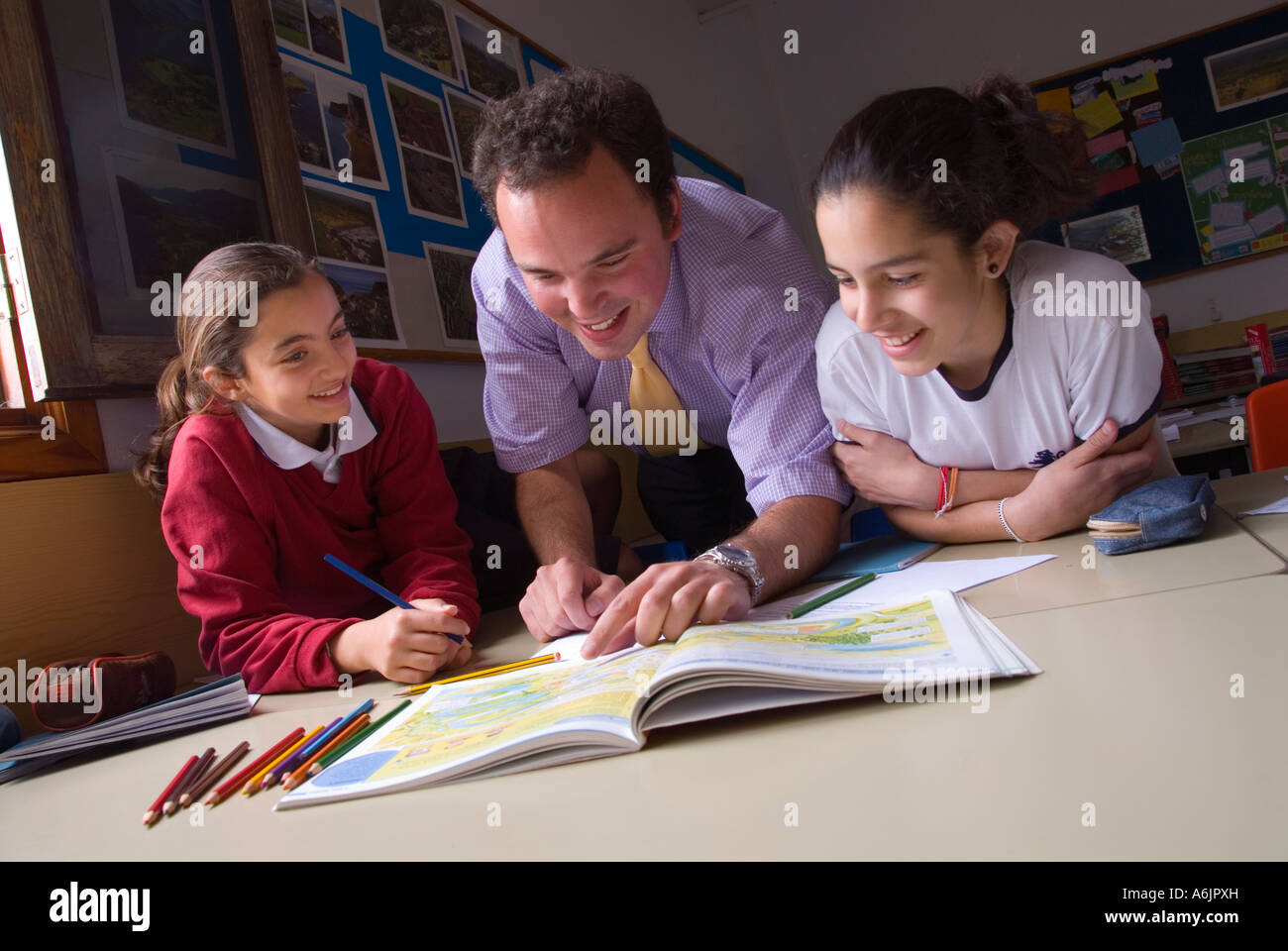 Teacher and junior pupils in school classroom happily interacting together on a geography mapping project Stock Photo