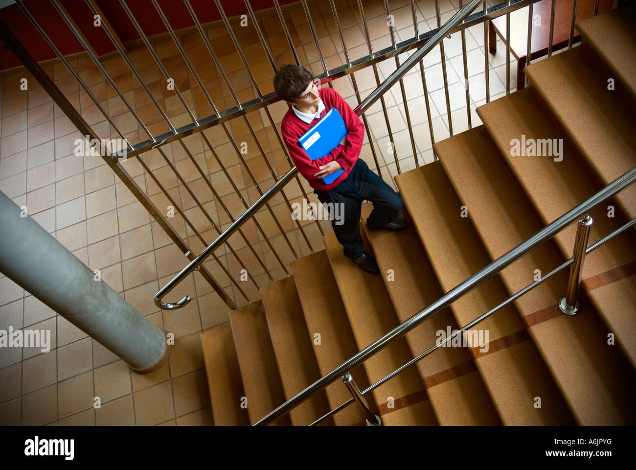 Junior schoolboy with school class study folder standing alone in school stairwell - Stock Image