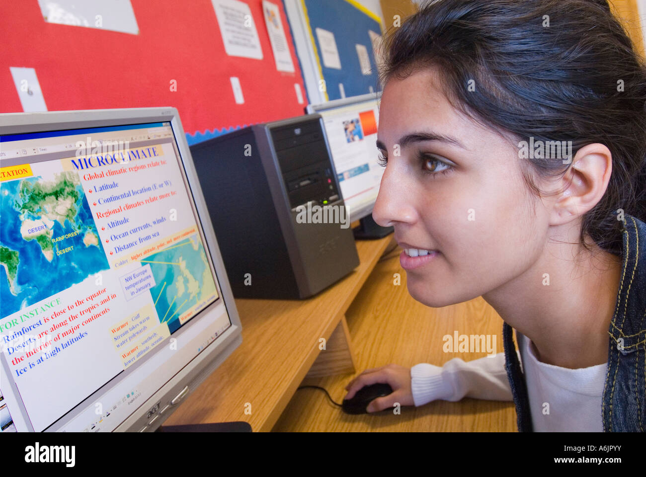 CLIMATE  CHANGE SCREEN STUDY SCHOOL asian teenage girl student working at her screen studying global weather climate issues in  computer classroom Stock Photo