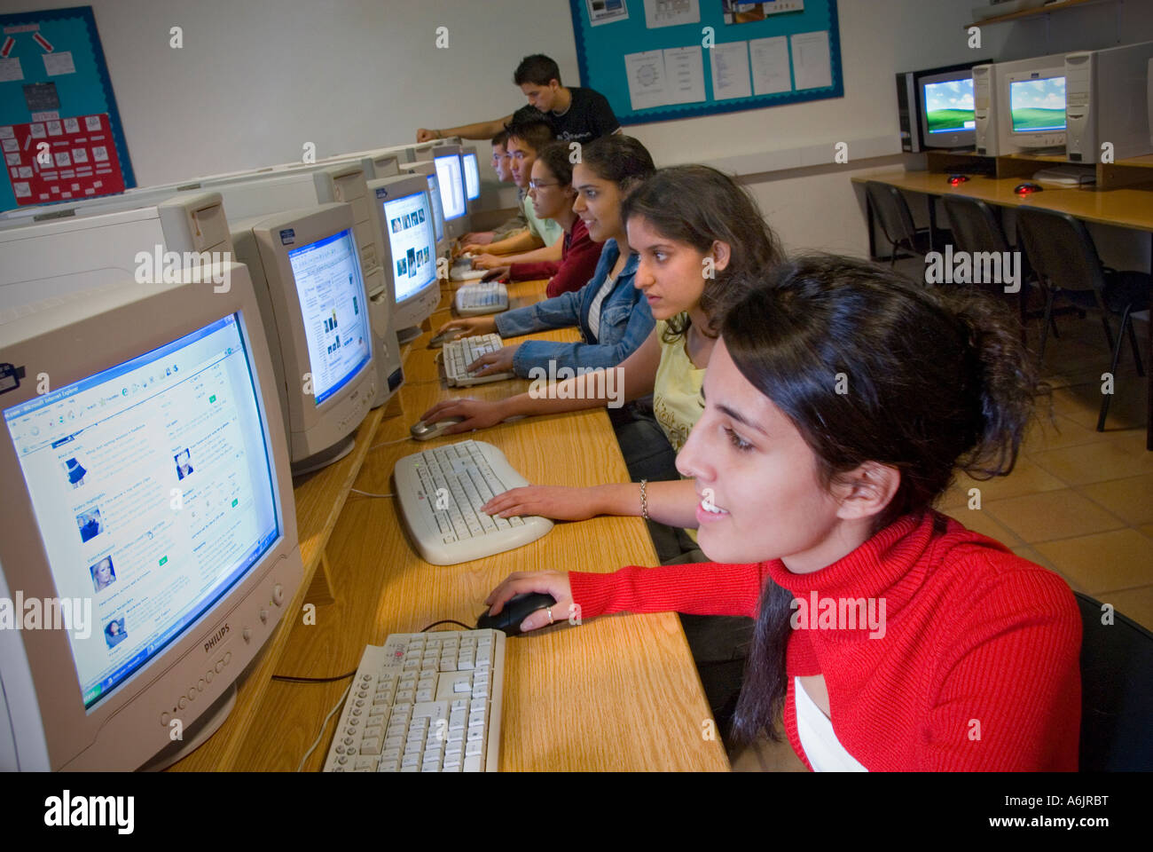 Multiracial senior teenage students studying at their work station screens in the school computer classroom - Stock Image
