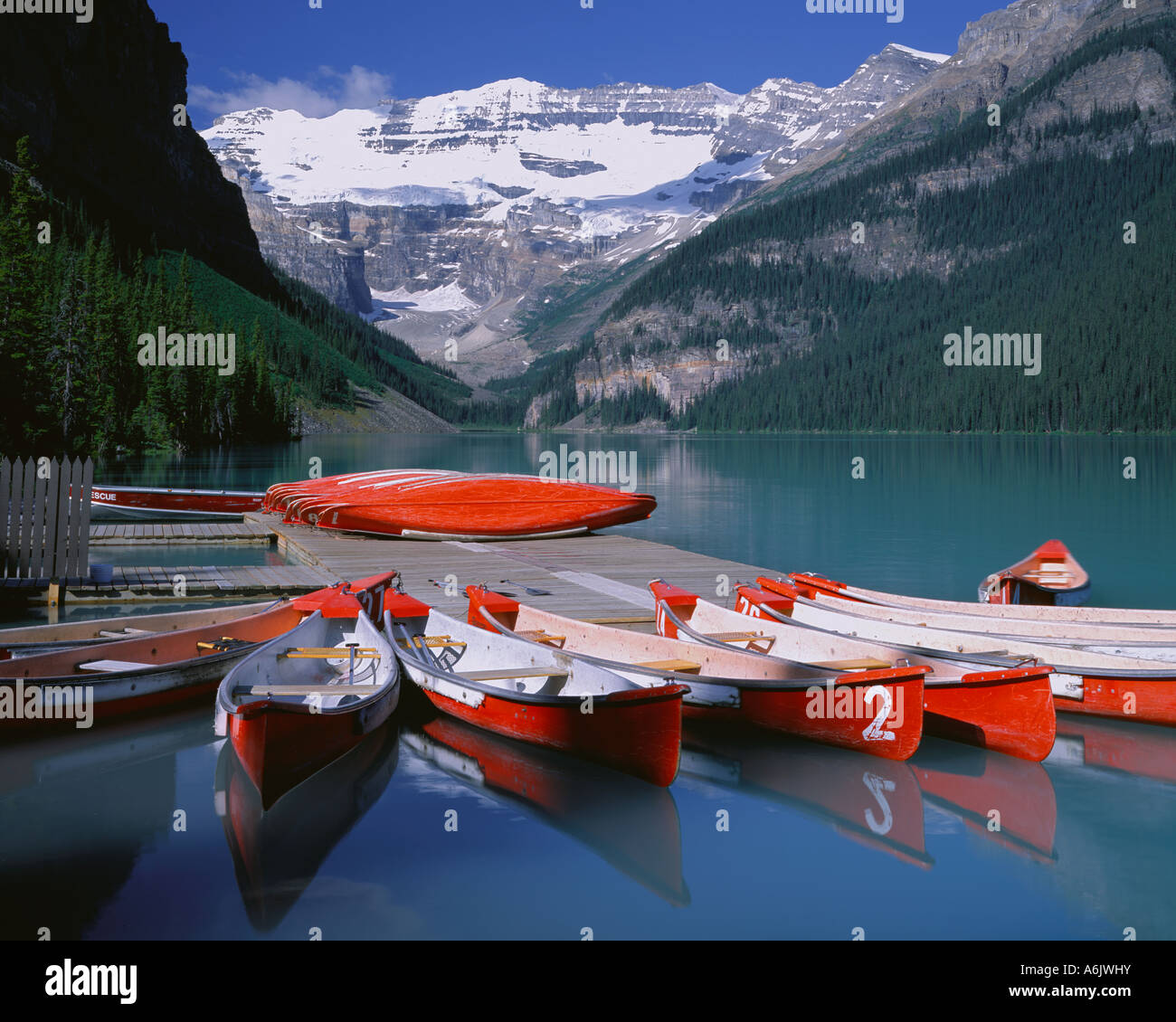 Banff National Park Canada: Red canoes on Lake Louise with Mount Victoria and Victoria Glacier in the distance - Stock Image