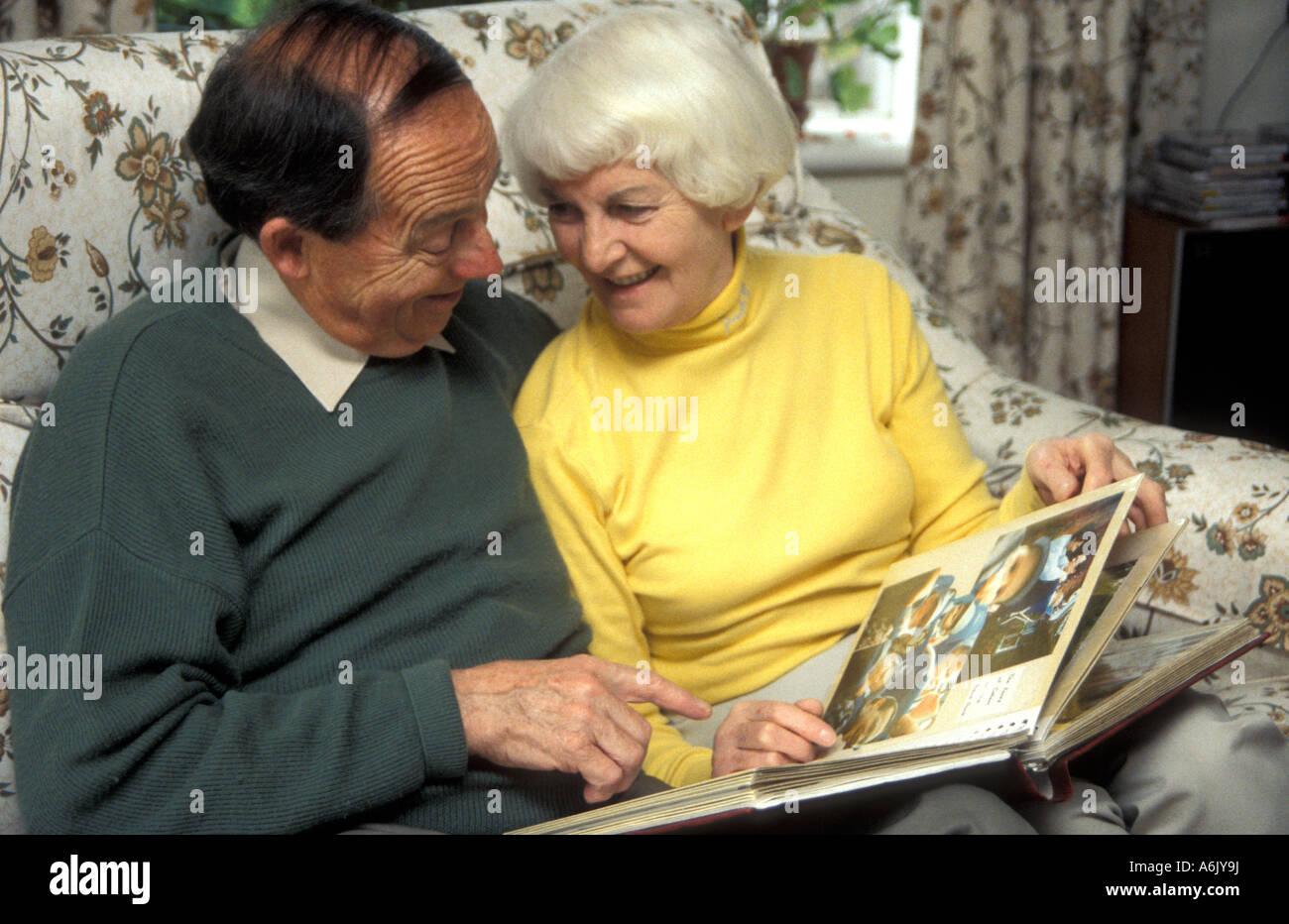 loving elderly couple sitting on sofa at home looking through photo album - Stock Image