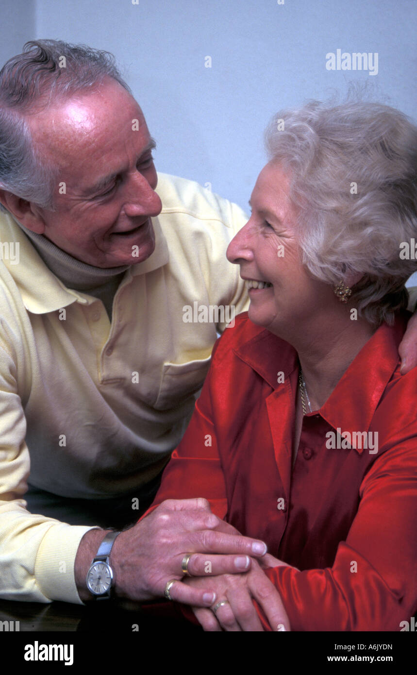 portrait mature couple having happy conversation and making eye contact - Stock Image