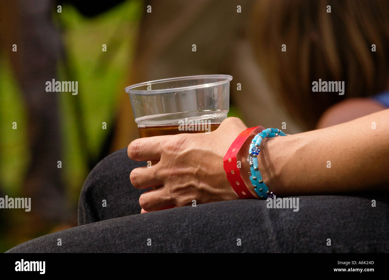 Close up of woman holding a pint of beer during the jazz festival in Brecon Powys Mid Wales UK - Stock Image