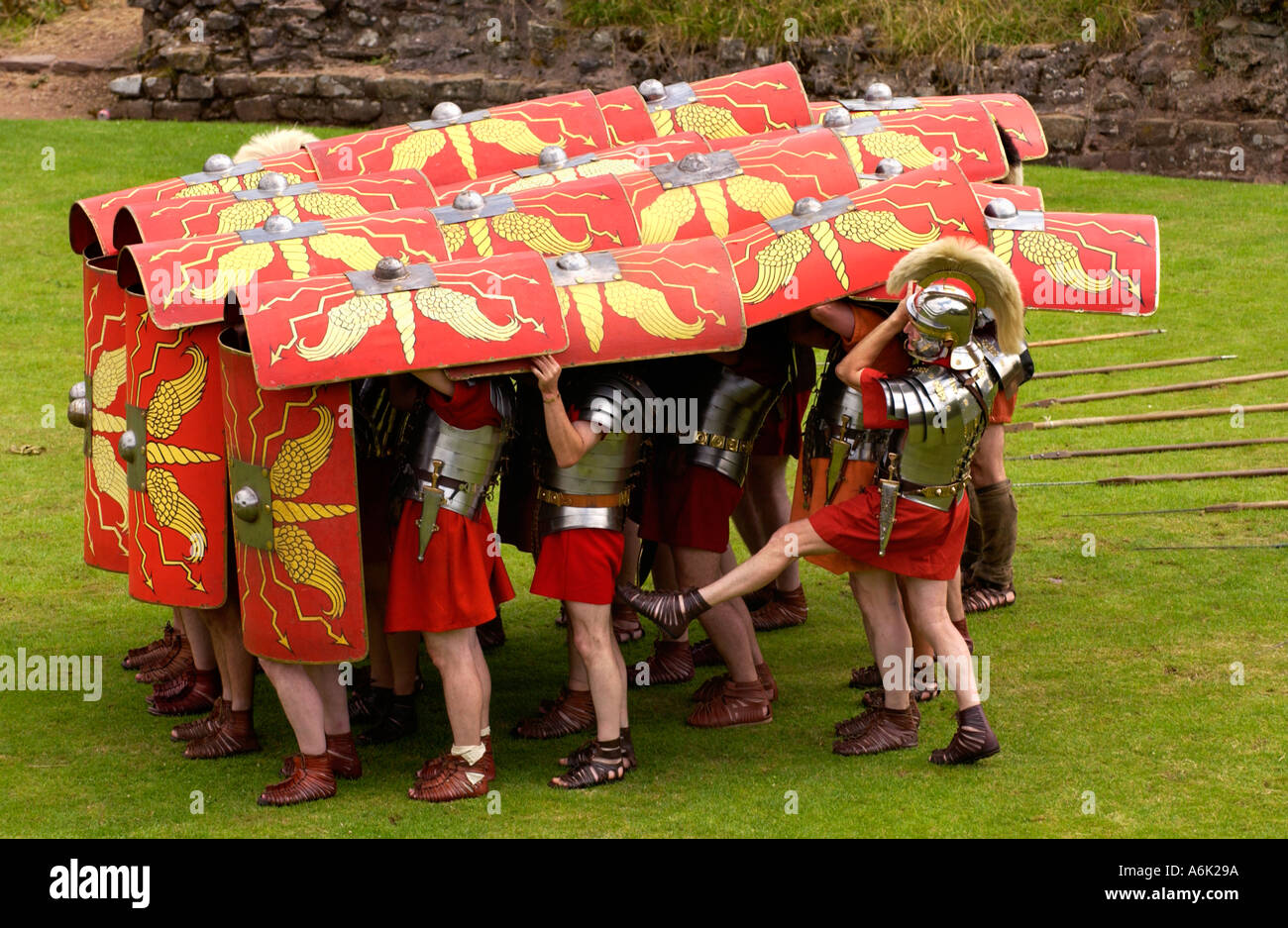 Ermine Street Guard demonstrate the tortoise defensive manoeuvre in display of fighting skills at Roman Amphitheatre Caerleon UK - Stock Image