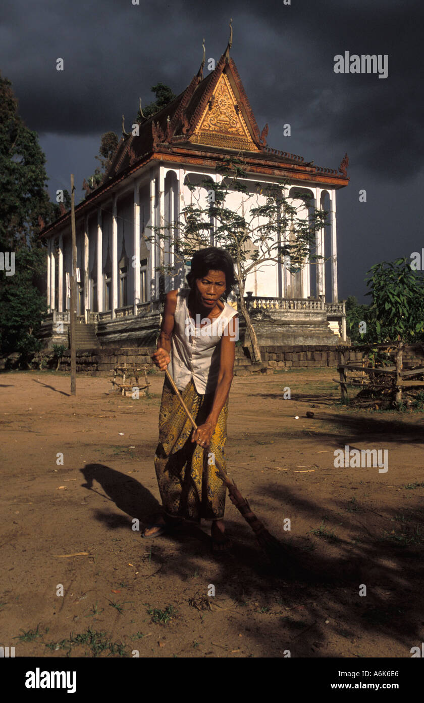 Cambodian woman sweeping in sunlight outside the pagoda in Mohar village as black sky shows storm approaching - Stock Image