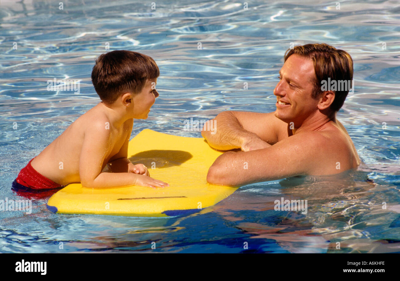 A father place with his five year old son who is floating on a Moray Boogy Board in a swimming pool  - Stock Image