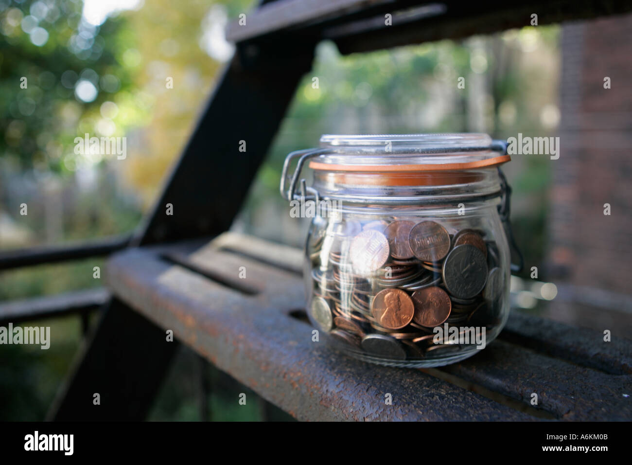 Jar filled with coins on fire steps close up Stock Photo