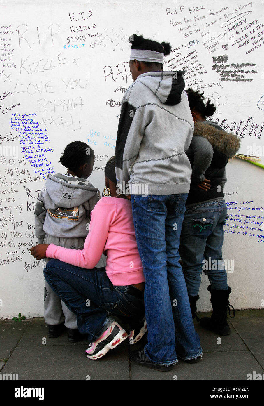 Mourners looking at written tributes to murdered teenager Kodjo Yenga who was stabbed to death in Hammersmith Grove - Stock Image