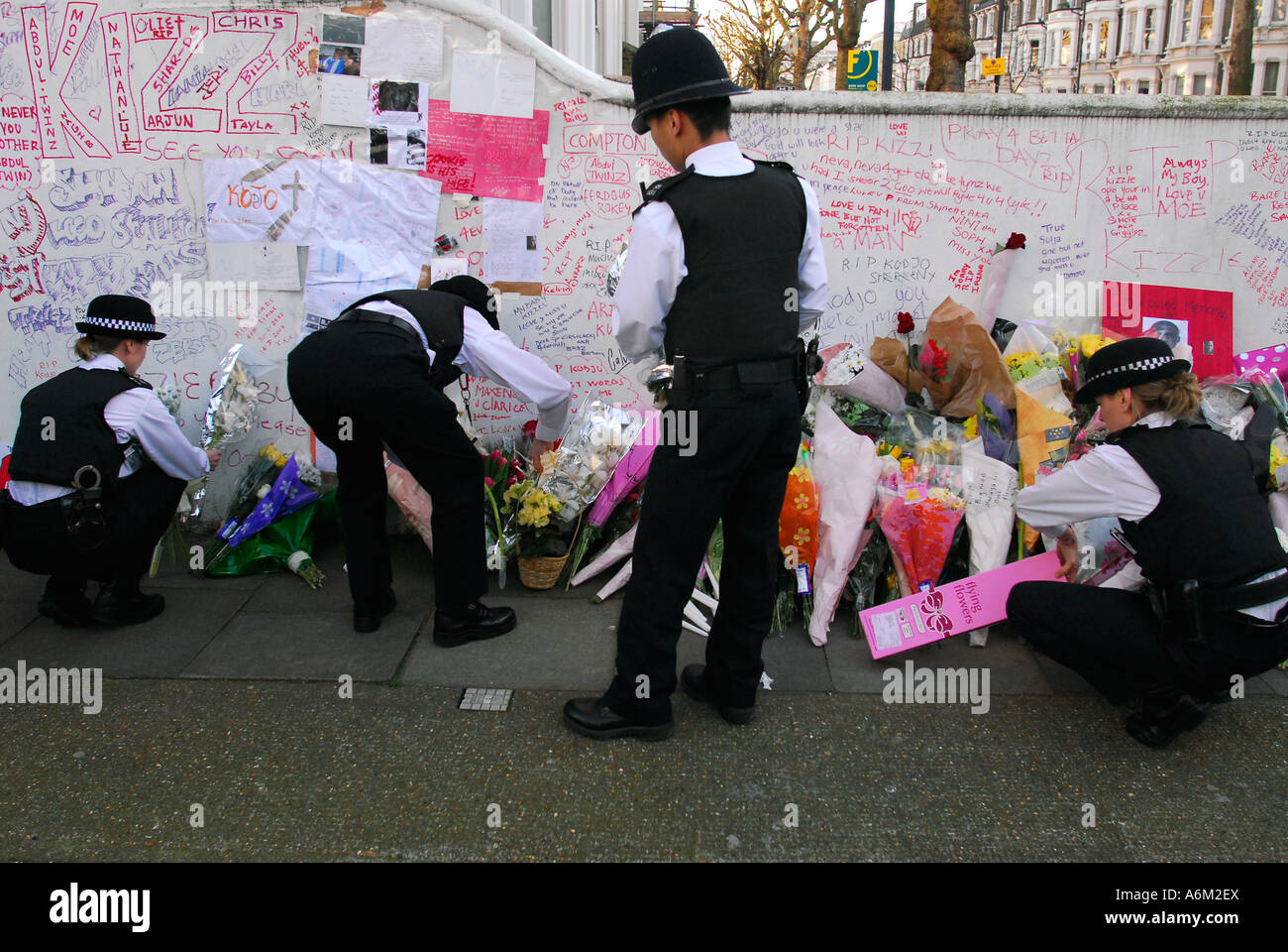 Police officers placing floral tributes to murdered teenager Kodjo Yenga who was stabbed to death in Hammersmith - Stock Image