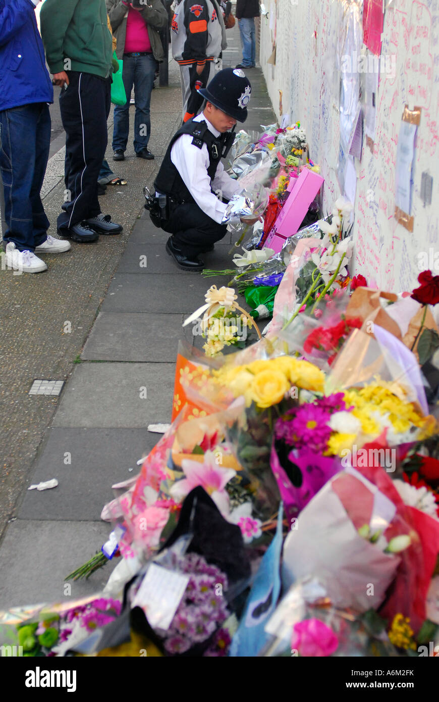 Police officer placing floral tributes to murdered teenager Kodjo Yenga - Stock Image