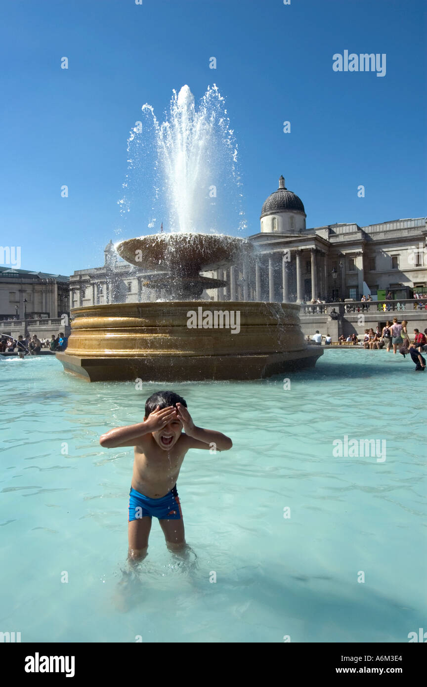 Young child cooling off in fountain during heat-wave at Trafalgar Square Central London - Stock Image
