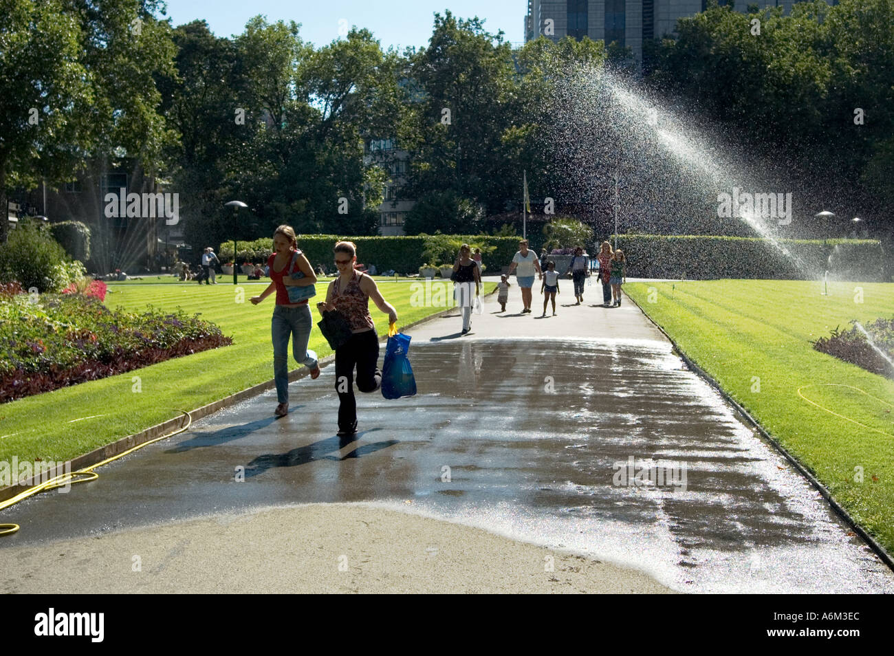 Girls dodging water sprinklers during a heat wave Victoria Embankment Gardens Central London - Stock Image