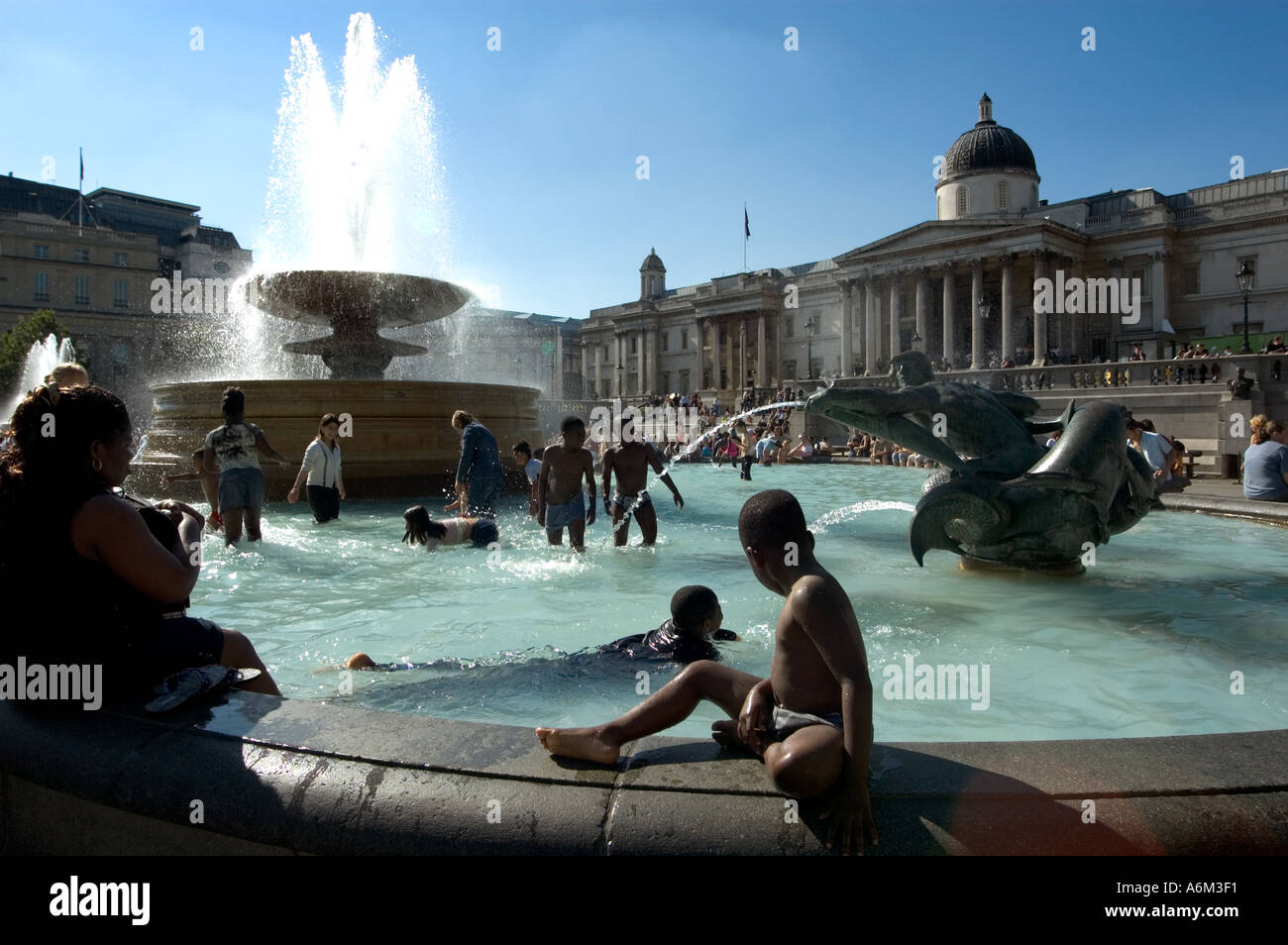Young children cooling off in fountain during heat-wave at Trafalgar Square Central London - Stock Image