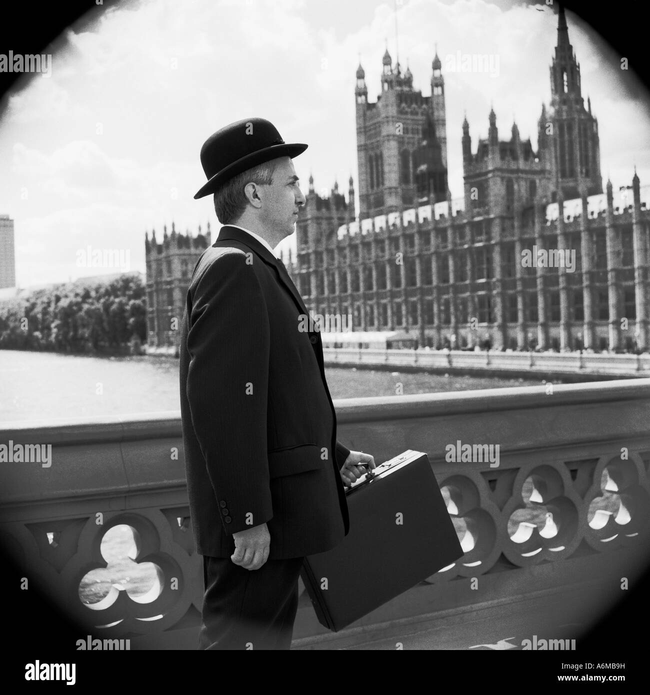 Englishman in bowler hat on Westminster bridge with Houses of Parliament - Stock Image