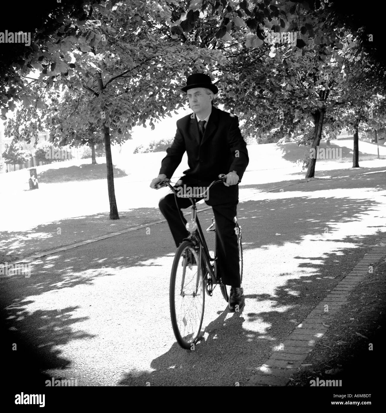 Englishman cycling on bike wearing traditional suit and bowler hat - Stock Image