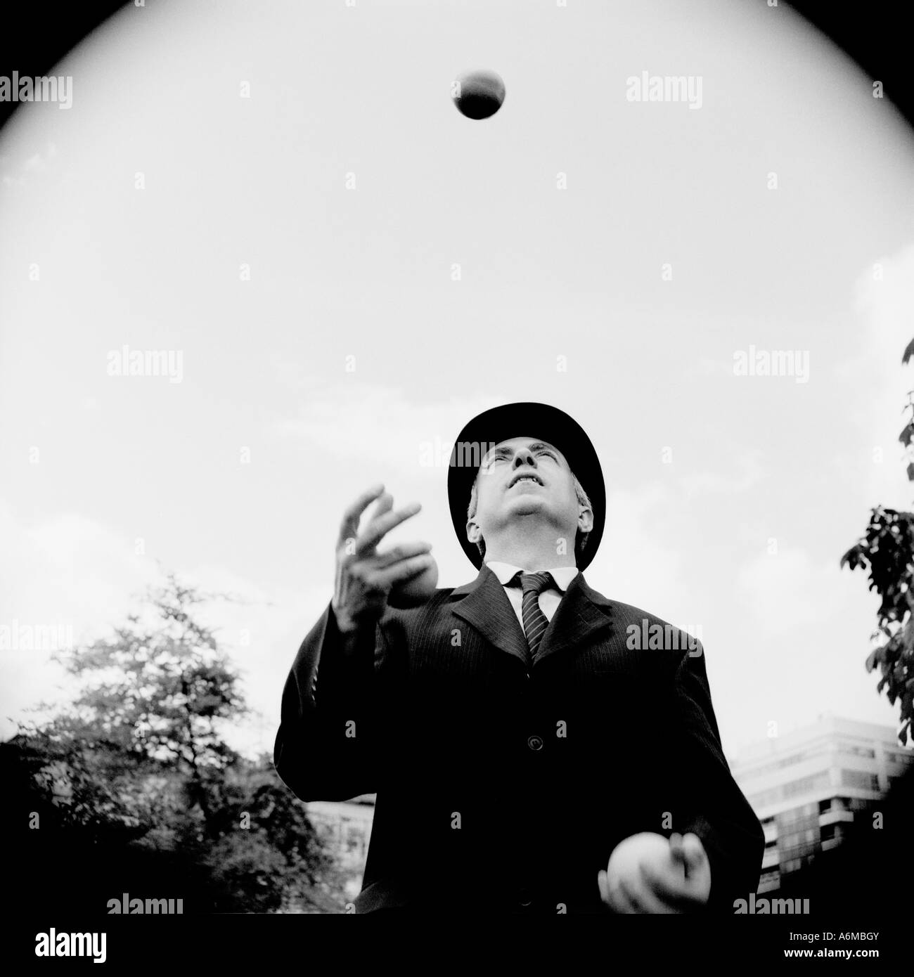City gent in bowler hat juggling - Stock Image