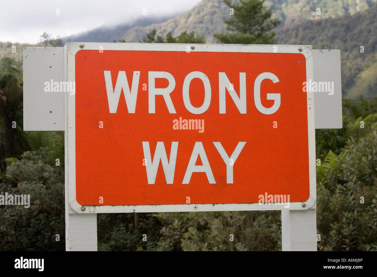 Bright red sign wrong way Franz Josef glacier Westland National Park South Island New Zealand - Stock Image
