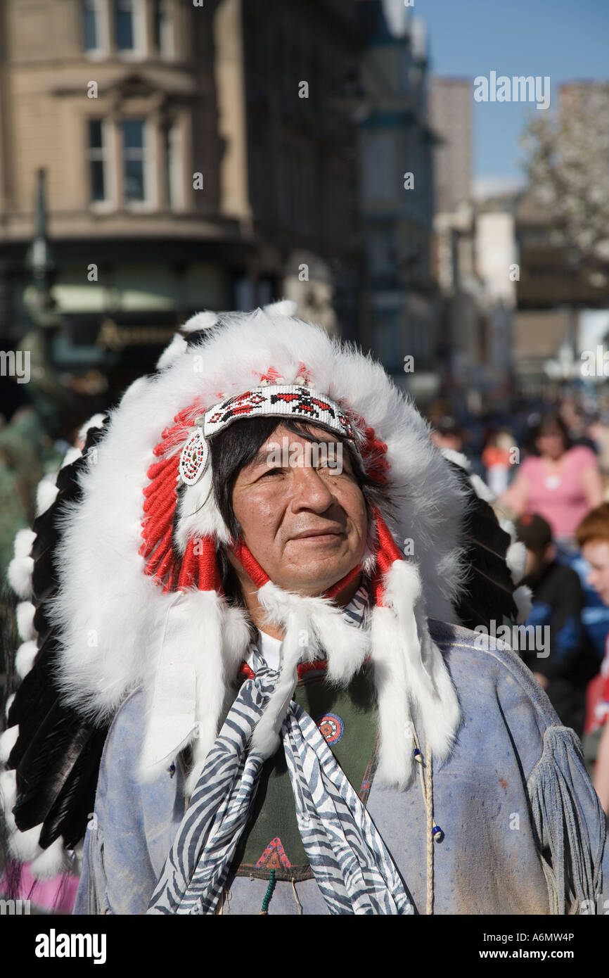 Mexican Indian musician wearing traditional ethnic feathered headdress. Musical street entertainer &  Vendor, - Stock Image