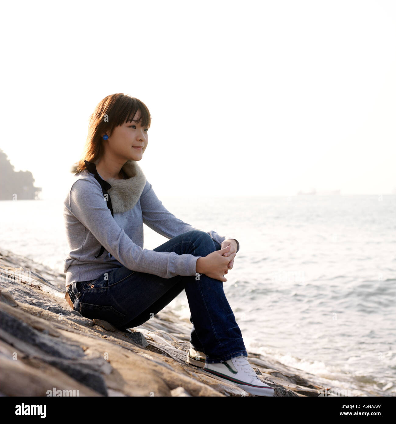 Girl sitting on rocks facing ocean - Stock Image