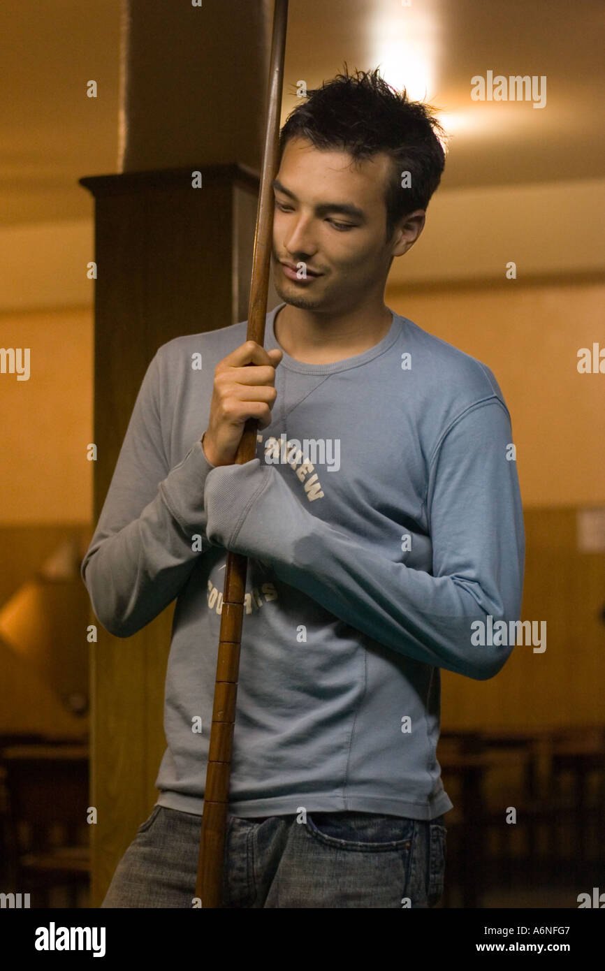 Bored young man leaning on a snooker cue with eyes closed in a Buenos Aires pool hall Stock Photo