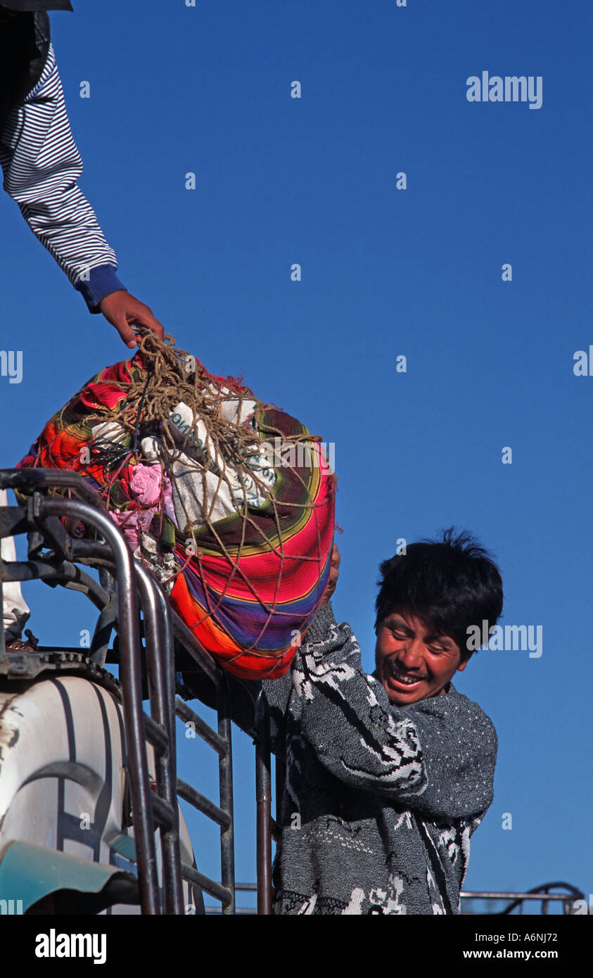 Loading luggage onto the roof of a Guatemalan public bus Quezaltenango Guatemala Central America - Stock Image